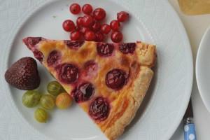 Auf dem Teller gelandet und auf den Verzehr wartend ein Stück Sauerkirschkuchen mit Begleitung aus Stachelbeeren, roten Johannisbeeren und einer späten Erdbeere.